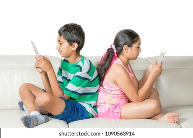 Children Engrossed in Their Respective Tablets on a Couch, Isolated, White