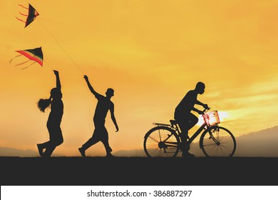 children enjoy flying a kite with ride bicycle during sunset.