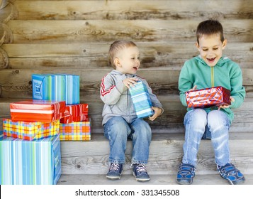 children enjoy gifts. Two cute brothers are happy with gifts