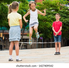 Children enjoy skipping on chinese jumping rope in urban playground in park