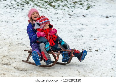 Children enjoy snowshoeing in the snow park where the grass comes out