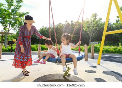 children enjoying in the playground with their mother