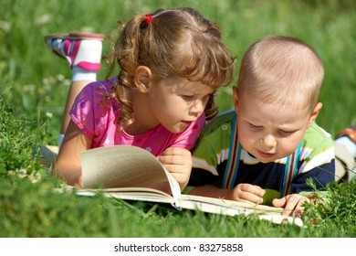 children enjoying reading the  book in green grass
