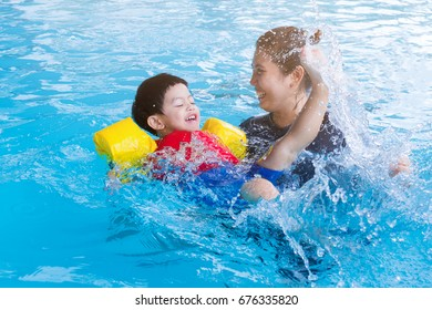Children are enjoying swimming in the pool. Happy little boy playing with outdoor swimming pool on hot summer day. Kids learn to swim.