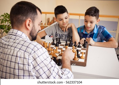 Children with Father playing chess at the table. the concept of childhood and board games, brain development and logic