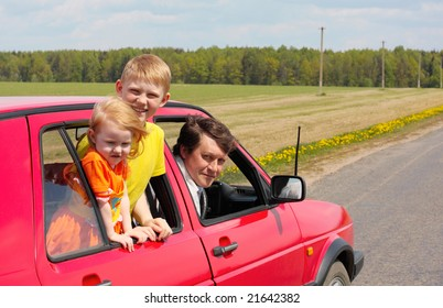 children with father in red car