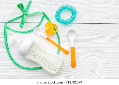 children feeding with breastmilk or infant formula powdered baby milk and toys on wooden background top view