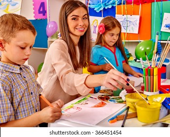 Children with female teacher painting on paper by paint and pencils  in  kindergarten .