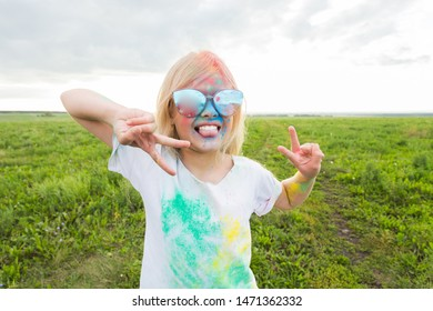 Children, festival of holi and holidays concept - happy little girl wearing sunglasses covered with color powder smiling over nature background