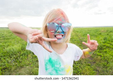 Children, festival of holi and holidays concept - happy little girl covered with color powder smiling over nature background