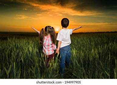 children in a field at sunset