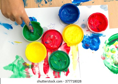 Children finger and paints on a table. children playing the colorful paints