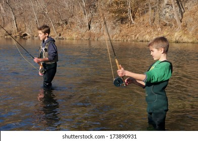 Children fishing - brothers and friends fly fishing in a clear stream (focus centered on boy casting in foreground)