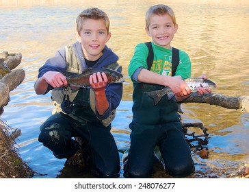 Children fishing - brothers and friends holding prize fish they caught fly fishing in a clear stream (Rainbow Trout)