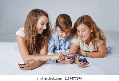 a children are focused on playing smartphones.