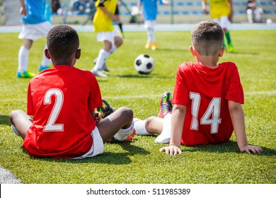 Children football soccer tournament. Kids playing football match. Two boys friends caucasian and african in red shirts watching soccer game competition.