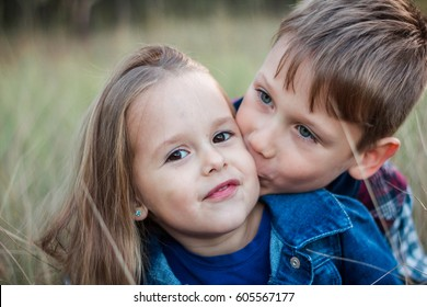 Children in the forest. The boy kisses the girl on the cheek