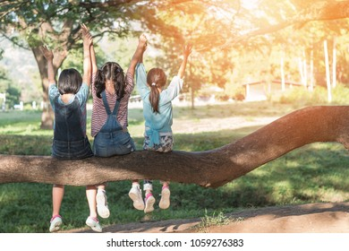 Children friendship concept with happy girl kids in the park having fun sitting under tree playing together enjoying good memory and moment of student friend lifestyle in school summer time day joy