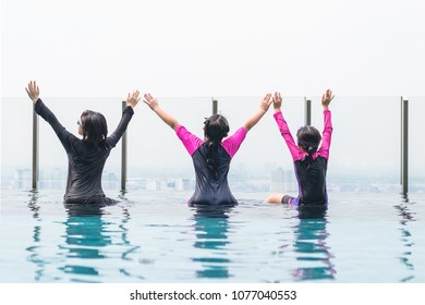 Children friendship concept with healthy happy school girl kid group back view having fun playing together in swimming pool on rooftop hotel or luxury condominium with city infinity skyline