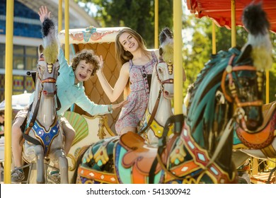 Children full of positive during their ride on the carousel with big toy horses. Family time for sister and brother during great summer day.