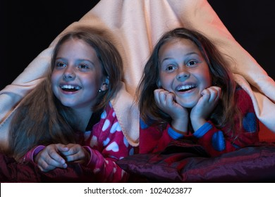 Children and fun time concept. Girls with excited faces. Girl friends watching TV in blanket tent. Kids wearing red jammies in bed on black background. PJs party for children.
