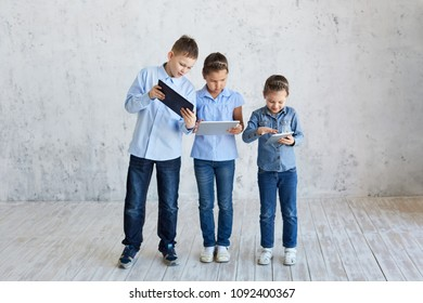 Children with gadgets. Three children play games on the tablet