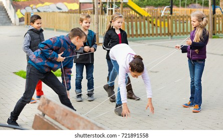 Children games. Cheerful positive girl goes through the tangled rope
