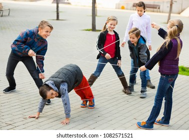 Children games. Smiling positive girl goes through the tangled rope