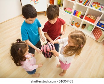Children gathering piggy-banks into a net