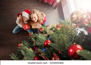 Children with gift under christmas tree