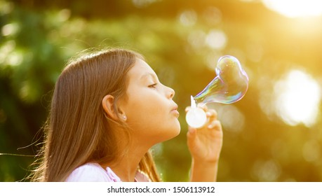 Children girl blowing soap bubbles outdoor