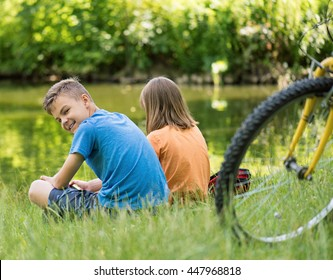Children - girl and boy, at lakeside. Family - brother and sister, have rest near water in park. Friends resting after biking.