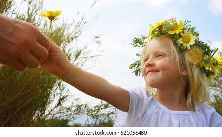 Children girl with daisy flowers. Summer vacation time. Country side.