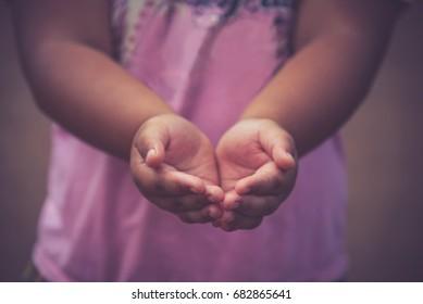 A children girl open hand begging for money