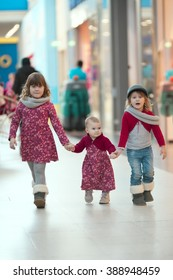 children Girls sister walk along the mall, playing in a big store, a family shopping trip