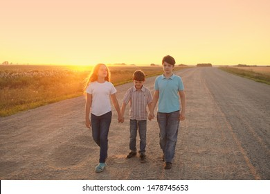 Children go on the road to meet the sunset. Freedom, movement, loneliness, humility concept.