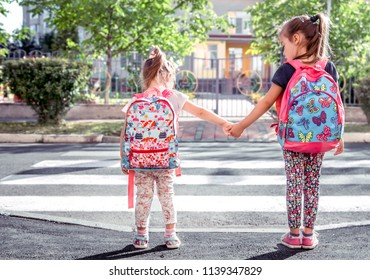 Children go to school, happy students with school backpacks and holding hands together, cross the road, the concept of education with girls