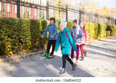 children go to school on the sidewalk with a fun company