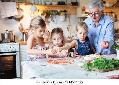 Children and grandmother cooking pizza in cozy home kitchen for family dinner. Cute kids girls are preparing homemade italian food. Three little sisters are helping senior woman. Lifestyle moment.