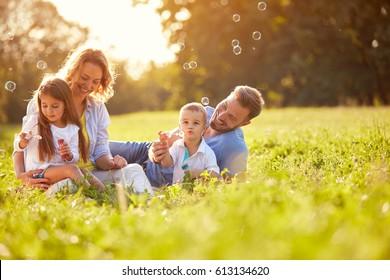 Kinder in grüner Natur machen Seifenblase im Sommer