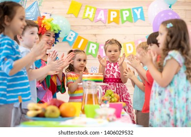 Children group with clown clown clap around table with birthday cake