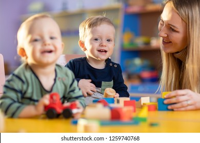 children group playing with teacher in day care centre nursery playroom