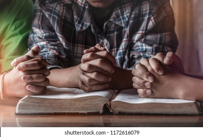Children group praying on wooden table with open holy bible, prayer meeting concept