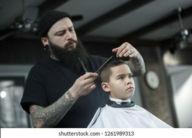 Children hairdresser cutting little boy against a dark background. Contented cute preschooler boy getting the haircut.