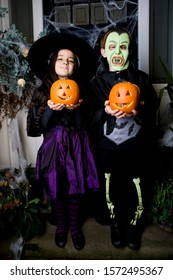 Children in Hallowe'en costumes, holding pumpkins with carved faces