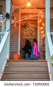 Children in Halloween costumes  knocking on door of decorated  neighborhood  fun trick or treat halloween night. Kids on Halloween trick or treat happy holiday.
