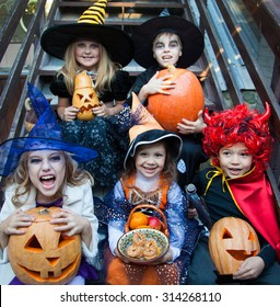 children in halloween costumes with pumpkin sit on the stairs