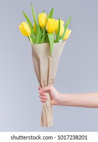 Children hand holding flowers over gray background. Bouquet of yellow tulips for Birthday, Happy mothers or Valentines day.