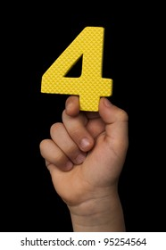 Children hand holding the number Four. Black isolated yellow number Four