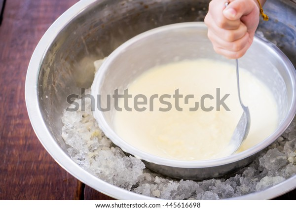 Children hand making home made ice cream with iced bowl. Spinning steel bowl for making Vanilla Ice Cream.
